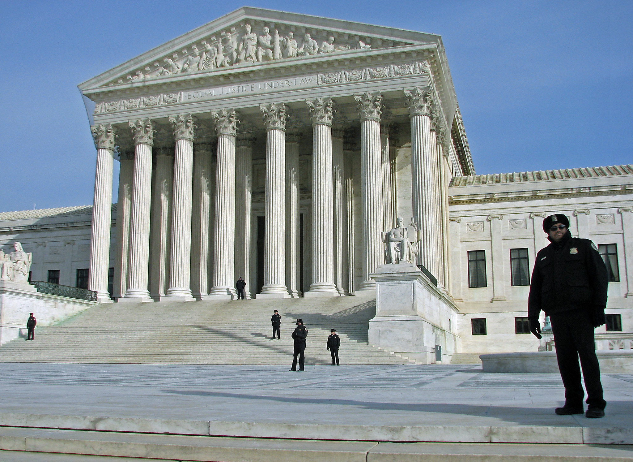 Supreme Court building with police officer standing on plaza