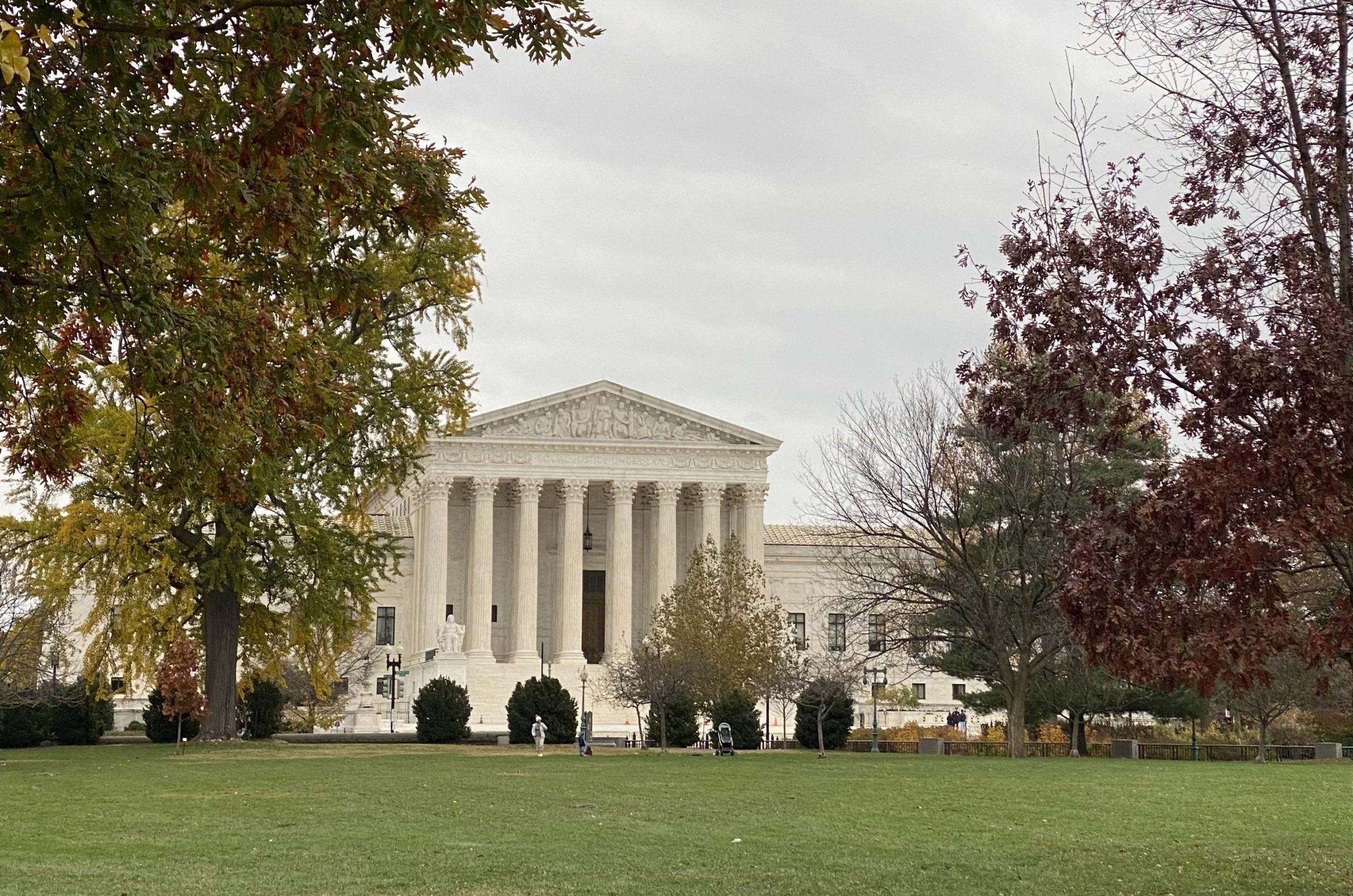 Supreme Court building seen from a distance surrounded by trees