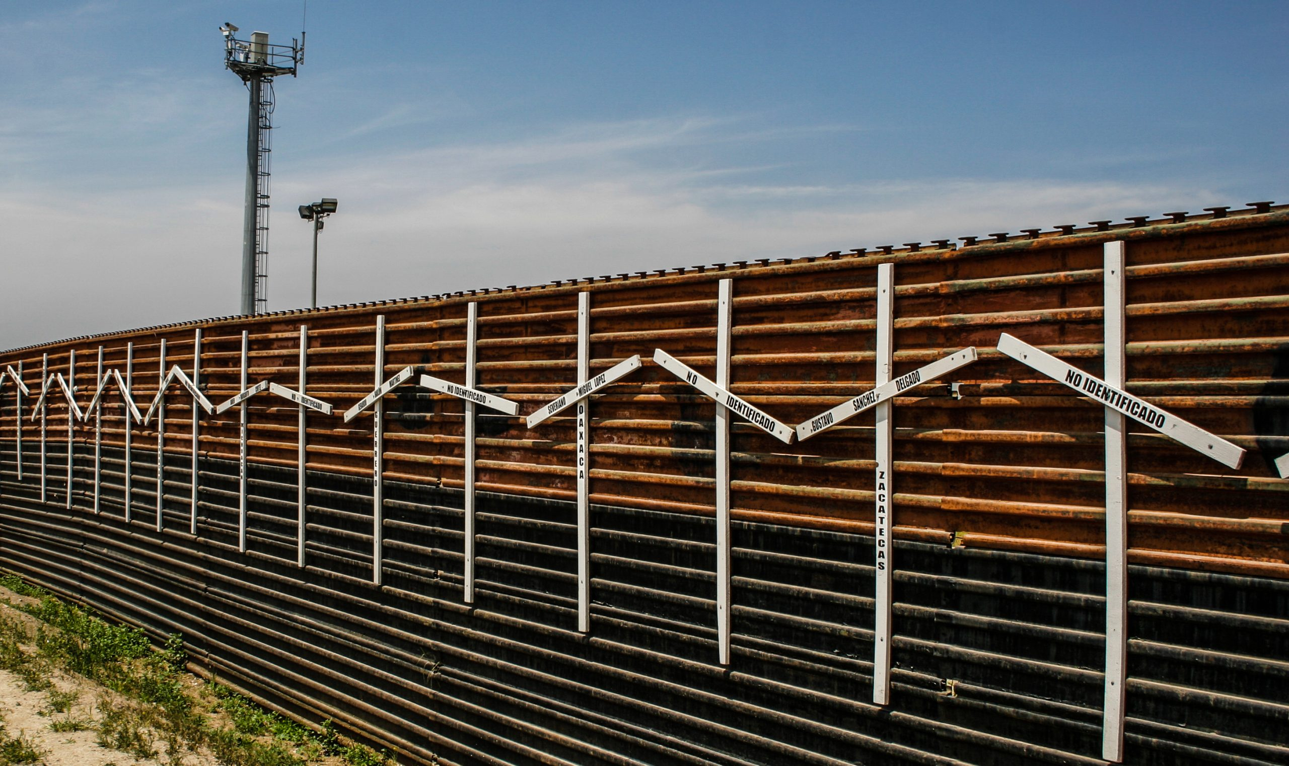border wall with surveillance tower in background