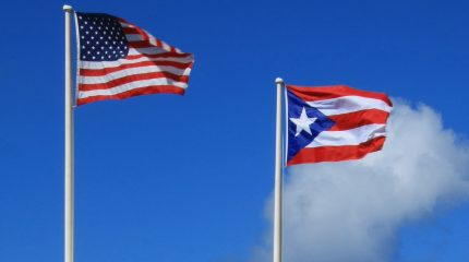 American flag and Puerto Rico flag against blue sky
