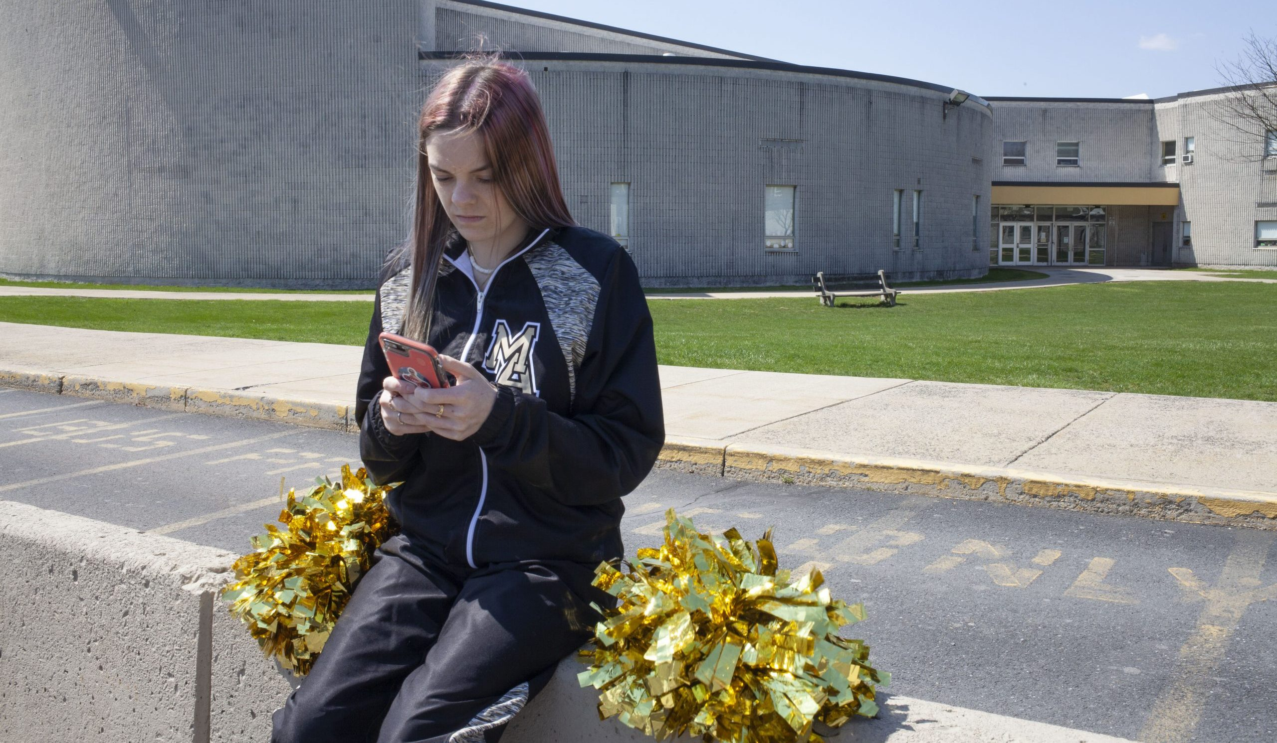 student holding phone and sitting in front of high school with cheerleading pom-poms beside her