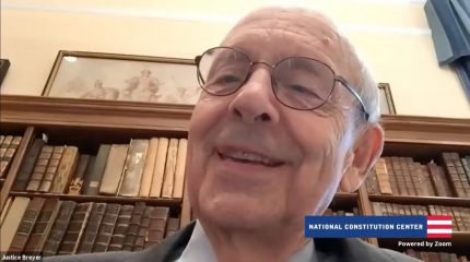 Screenshot of Stephen Breyer's face with bookcase in background and National Constitution Center logo on screen