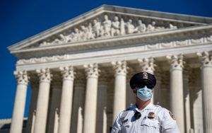 police officer in mask standing in front of supreme court building