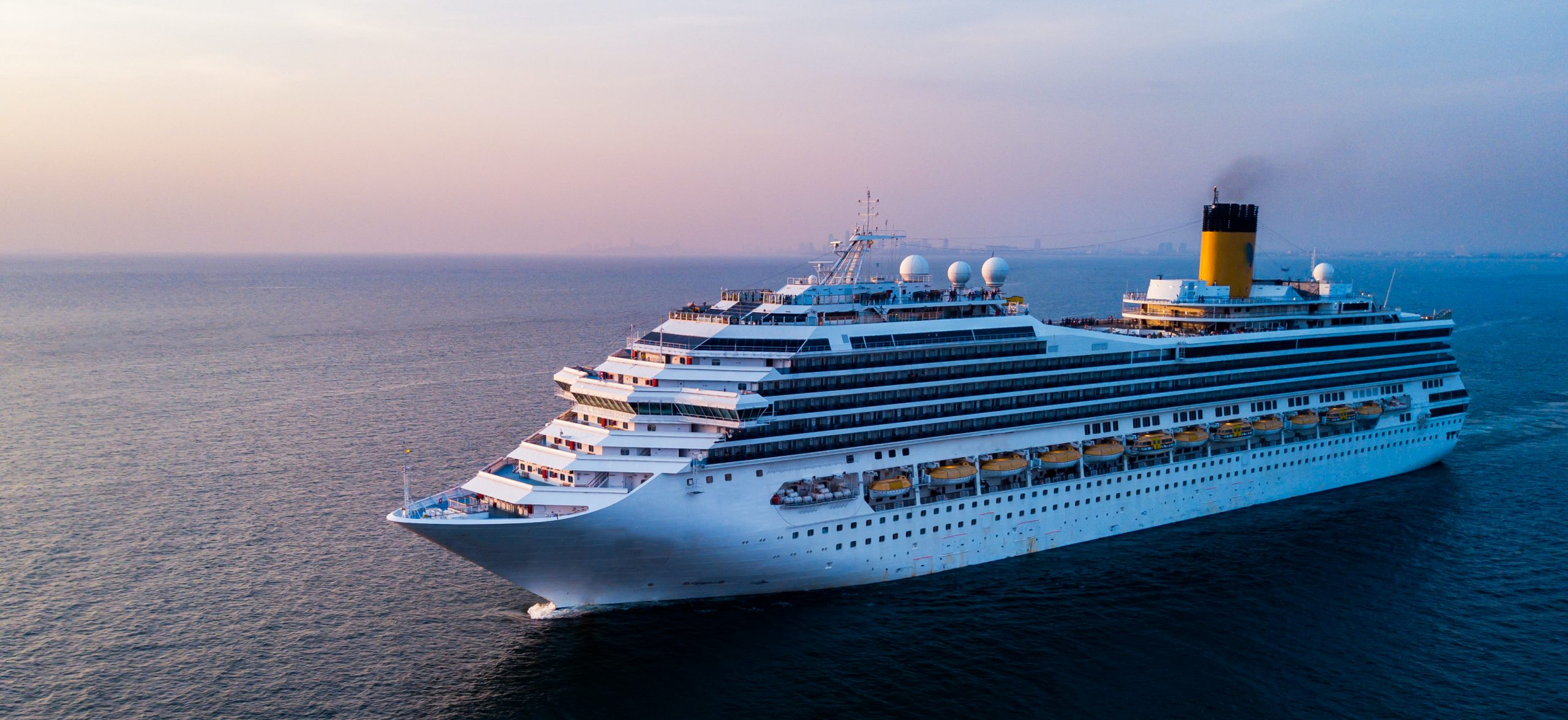 large cruise ship sailing in calm ocean water at sunset