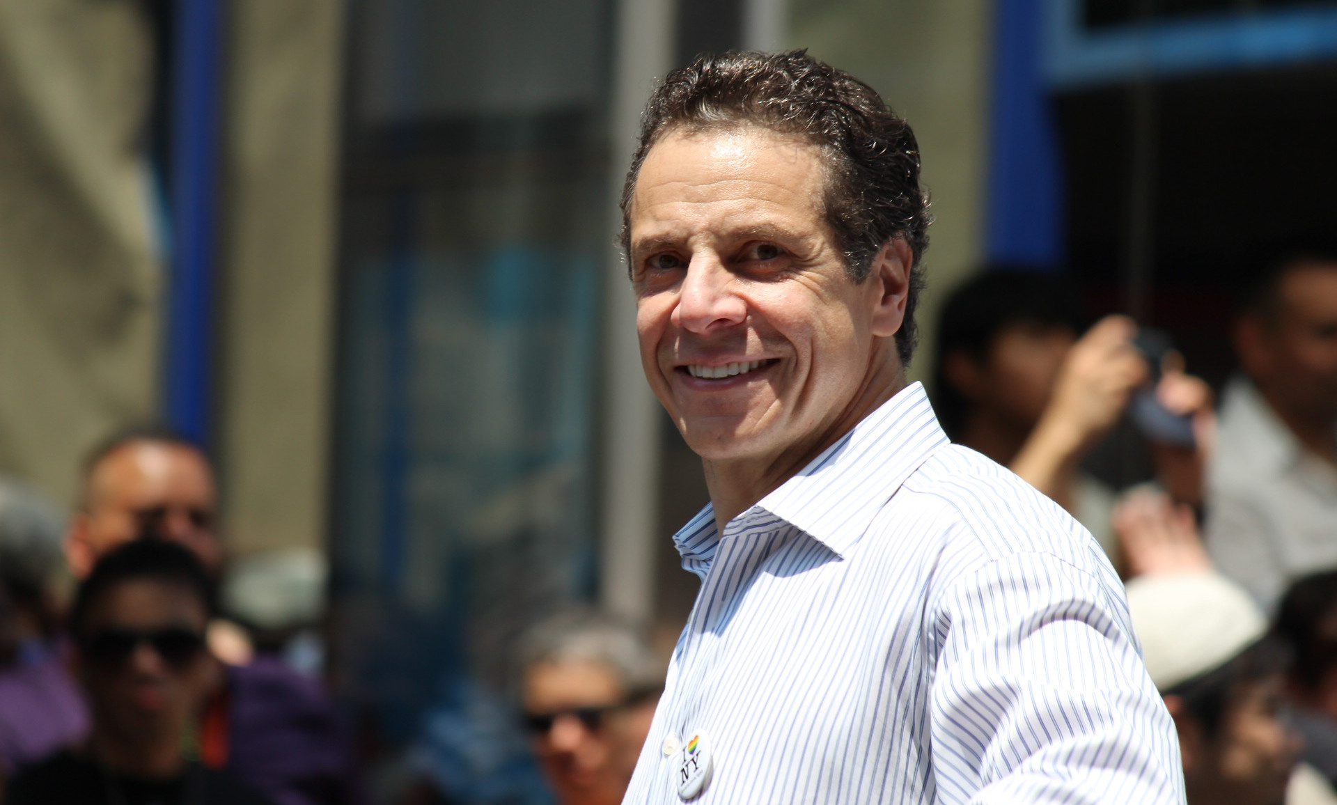 """andrew cuomo smiling in white button-down shirt with """"I love New York"""" pin"""