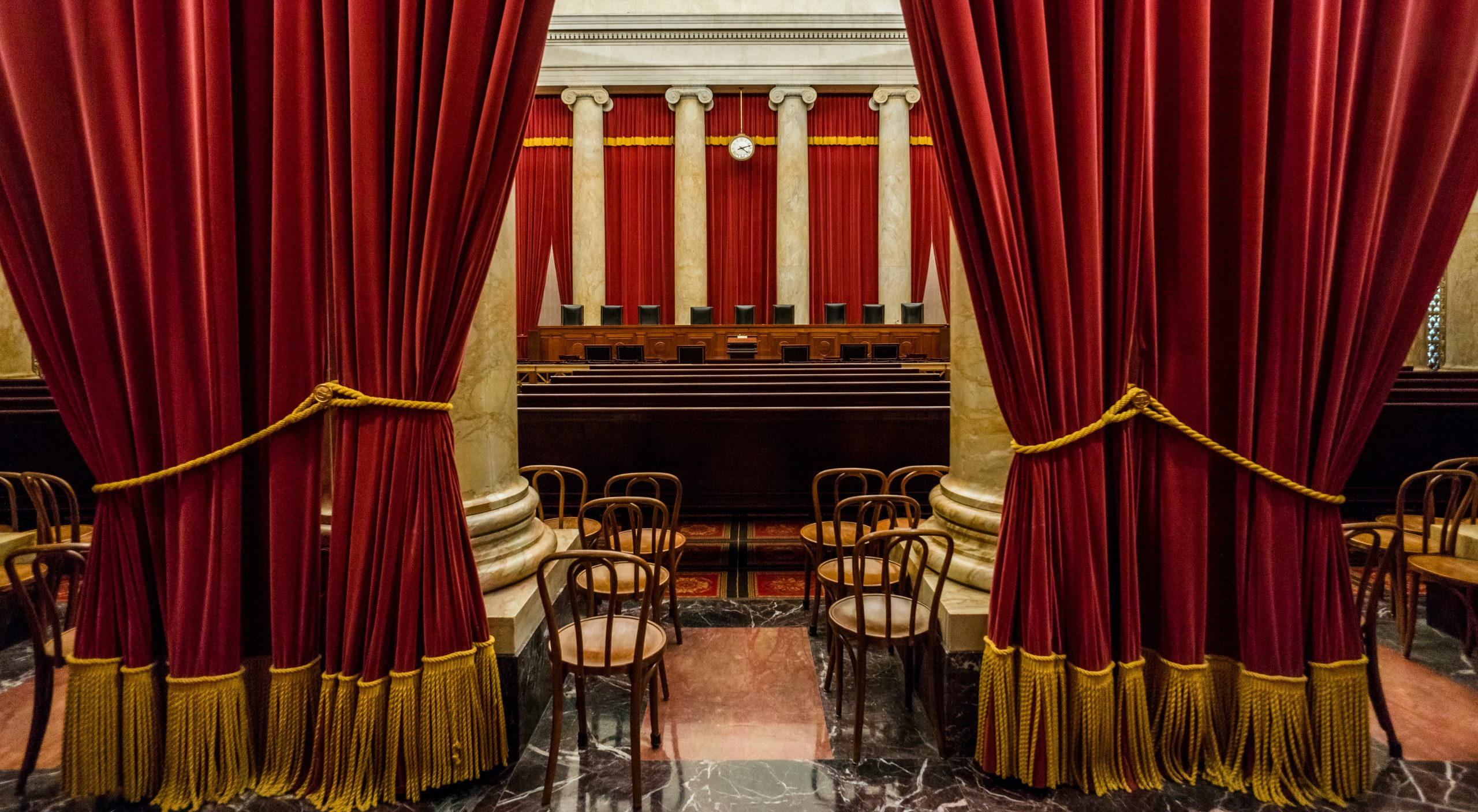 view of empty Supreme Court bench from back of courtroom with large curtains in foreground