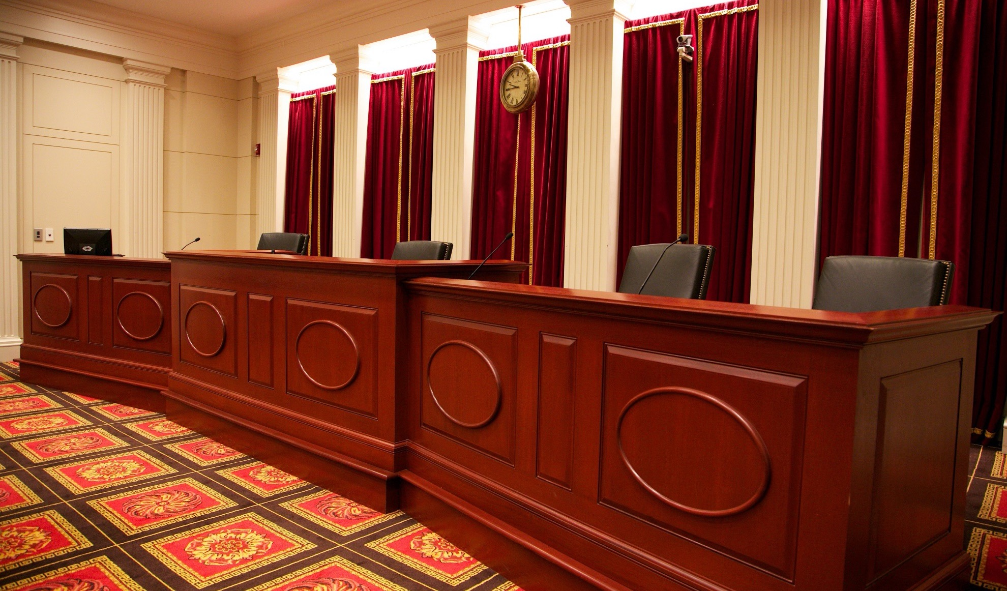large wood-paneled judges' bench with four chairs