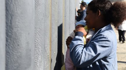 woman holding infant while standing a few inches from tall gray fence