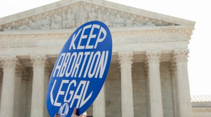 """two hands holding round sign reading """"Keep Abortion Legal"""" with Supreme Court building in background"""