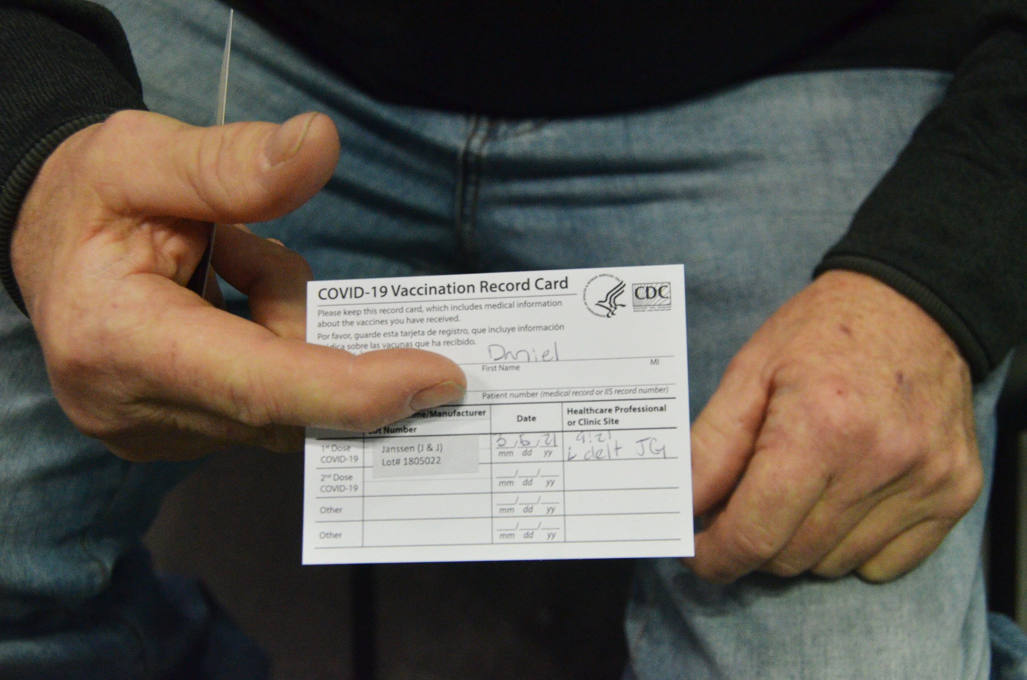close up photo of man's hands holding vaccine card