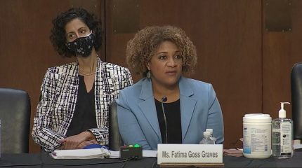 Fatima Graves speaking at senate hearing. Woman behind here in mask.