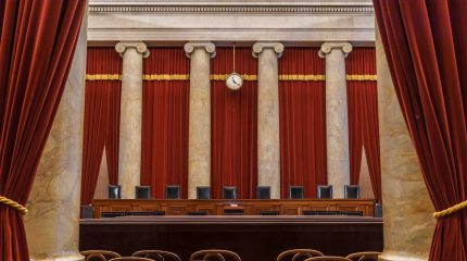 view of empty supreme court bench as seen from back of courtroom