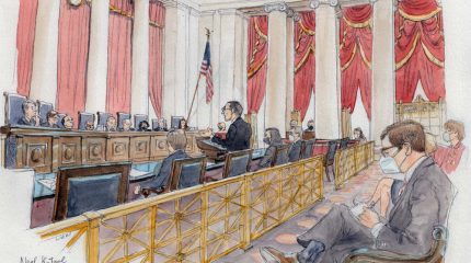 wide view of courtroom with nine justices sitting at bench, man standing at lectern, and several spectators wearing masks seated in gallery