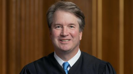brett kavanaugh wearing judicial robe and sitting with hands crossed in lap