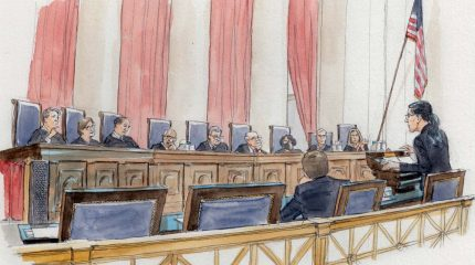 woman at lectern speaking to nine justices sitting on elevated bench